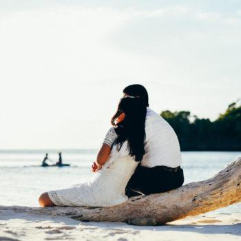 Majal and Regine Mirasol sitting at the beach. Honeymoon image.